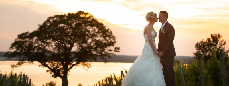 bride and groom holding hands with sunset